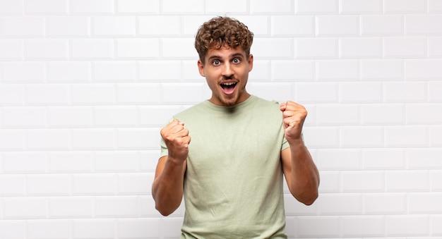 年轻人感到震惊,兴奋和快乐,笑着庆祝成功,说哇!