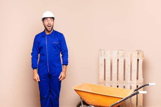 Молодой человек чувствует себя потрясенным, счастливым, удивленным и удивленным, глядя в сторону с концепцией строительства с открытым ртом
