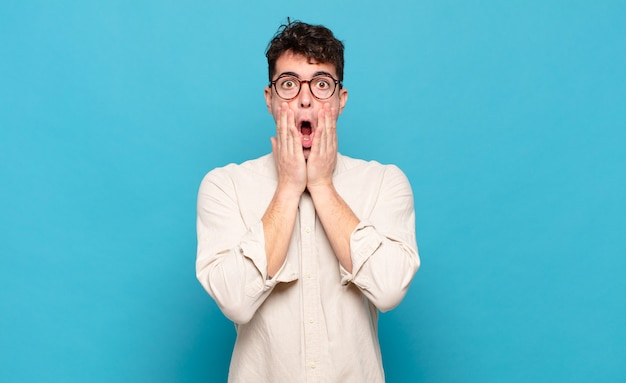 Young man feeling shocked and scared, looking terrified with open mouth and hands on cheeks