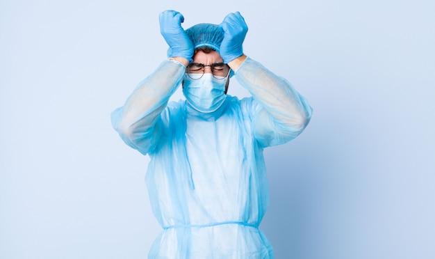 若い男がストレスと不安を感じ、落ち込んで頭痛で欲求不満になり、両手を頭に上げた。コロナウイルスの概念