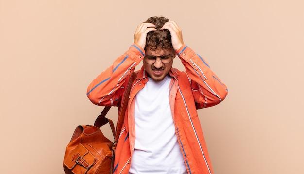 若い男はストレスと欲求不満を感じ、手を頭に上げ、疲れ、不幸、片頭痛を感じます