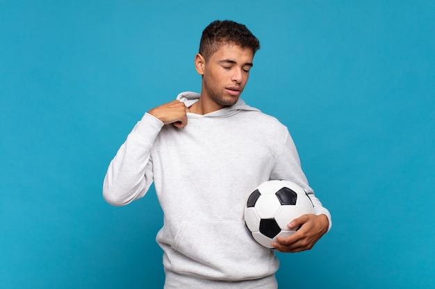 Молодой человек чувствует стресс, тревогу, усталость и разочарование, дергает рубашку за шею и выглядит разочарованным из-за проблемы. футбольная концепция