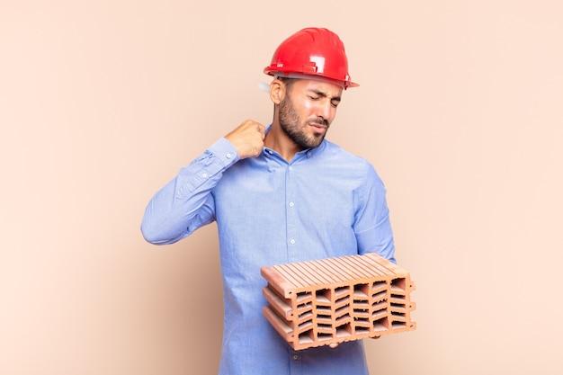 Молодой человек чувствует стресс, тревогу, усталость и разочарование, дергает за шею рубашки, выглядит разочарованным из-за проблемы
