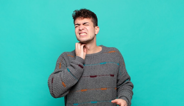 Young man feeling stressed, frustrated and tired, rubbing painful neck, with a worried, troubled look
