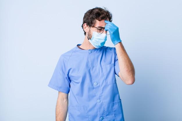 若い男は、ストレスを感じ、不幸でイライラし、額に触れ、激しい頭痛の片頭痛を患っています。コロナウイルスの概念