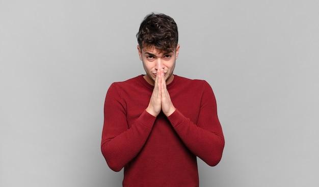 젊은 남자가 걱정스럽고 희망적이며 종교적이며 손바닥을 눌렀을 때 신실하게기도하고 용서를 구걸합니다.