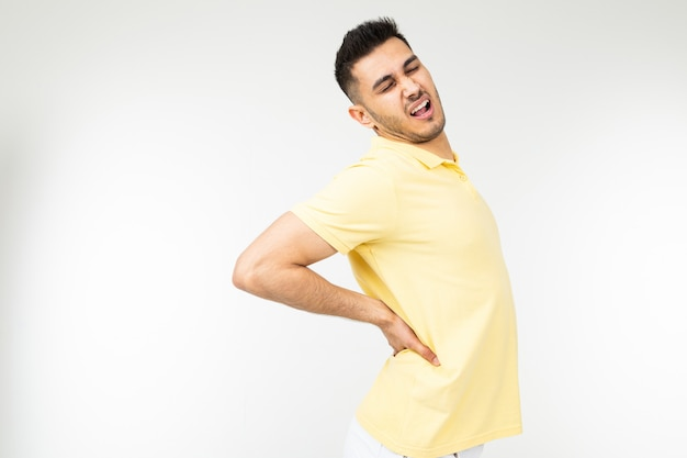 Young man feels back pain on a white studio background with copy space
