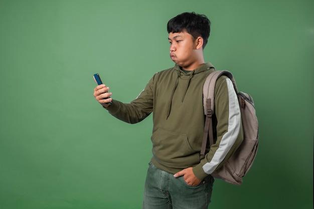 Молодой человек испытывает отвращение к тому, что показывают на смартфоне