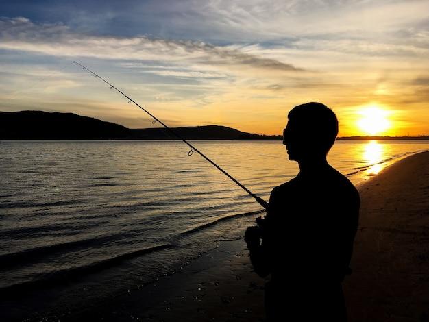 일몰에 호수에 낚시하는 젊은이