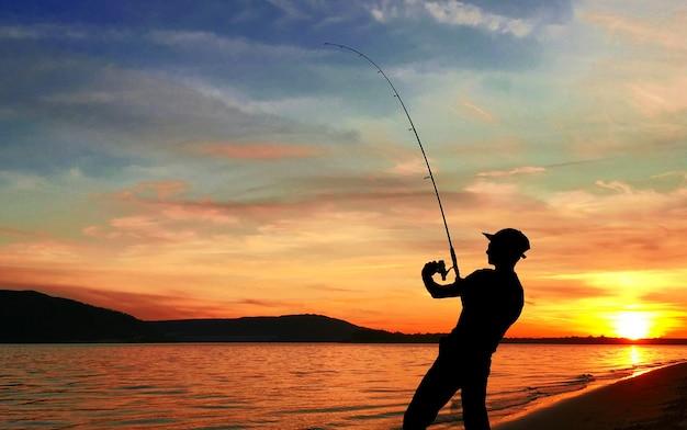 日没時に湖で釣りをする若い男