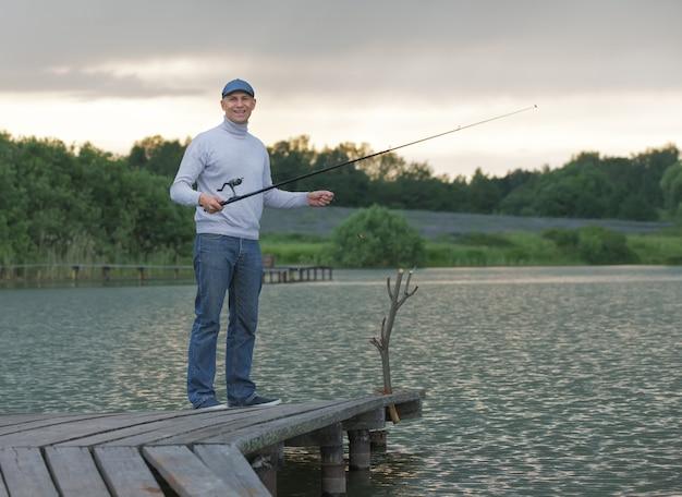 Молодой человек, ловящий рыбу на озере