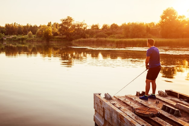 Young man fishing on river standing on bridge at sunset