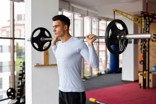 Young man at fitness class lifting weights