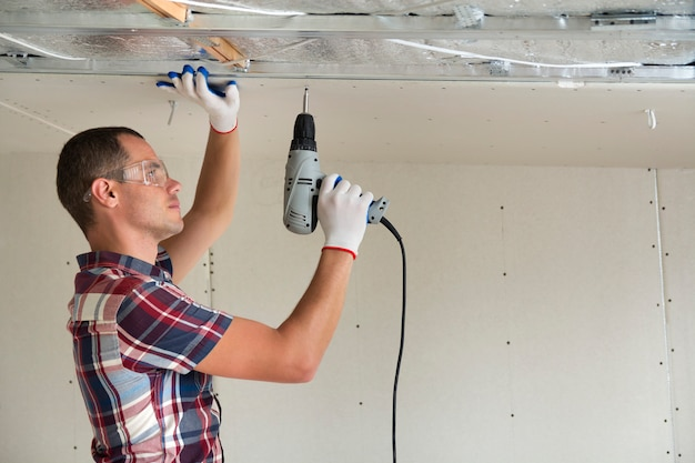Young man in fixing drywall suspended ceiling