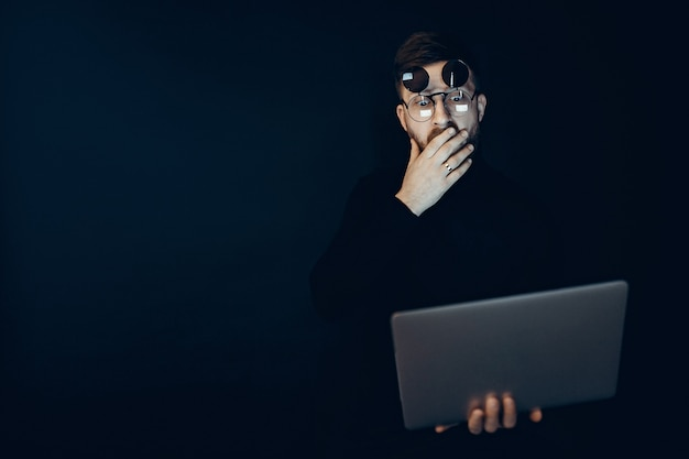 Young man in flip-up glasses holding laptop looking at it with shock on black wall