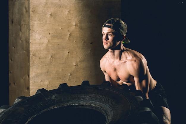 Молодой человек листает шины в тренажерном зале