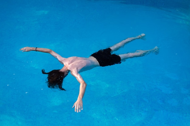 Young man floating and having fun in the swimming pool