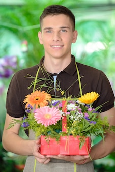Young man florist that cares for the flowers.