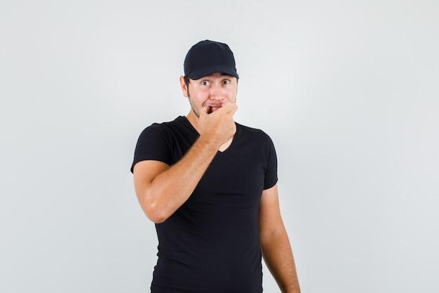 黒のtシャツで顔に笑顔を強制する若い男