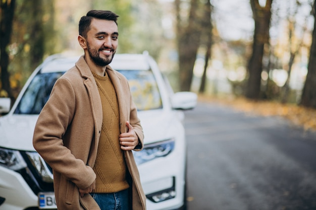 Young man in forest wearing coat by the car