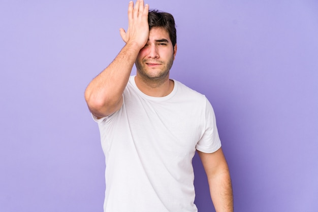 Young man forgetting something, slapping forehead with palm and closing eyes.