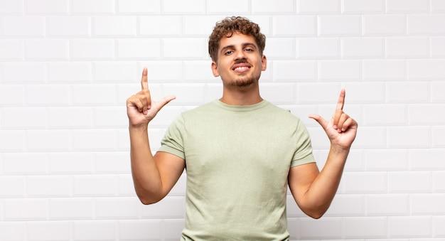 Молодой человек, обрамляющий или очерчивающий собственную улыбку обеими руками, выглядит позитивным и счастливым, концепция благополучия