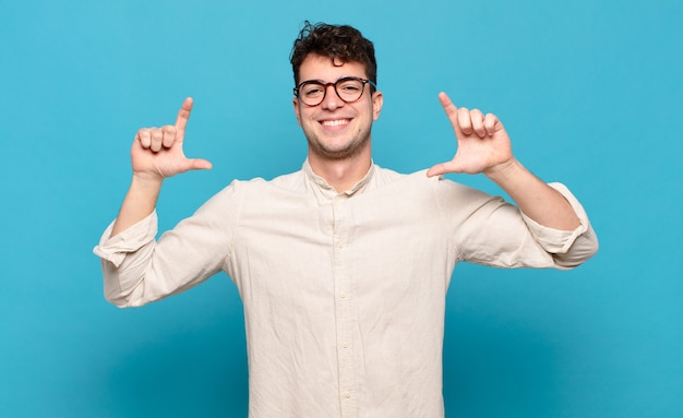 Young man framing or outlining own smile with both hands