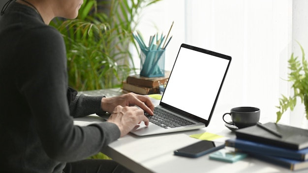 Young man freelancer sitting in comfortable workplace and using laptop computer.