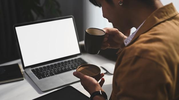 Фрилансер молодой человек сидит перед своим портативным компьютером и пьет горячий кофе.