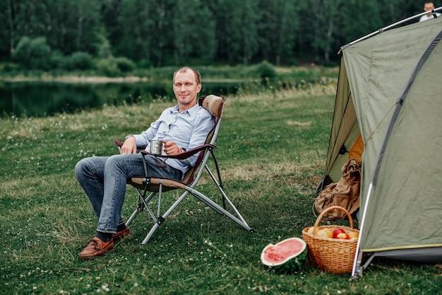젊은 남자 프리랜서 의자에 앉아 숲이나 초원에서 캠핑 사이트에서 텐트 앞에서 휴식. 여름철 야외 활동. 국립 공원에서 여행하는 모험. 레저, 휴가, 휴식