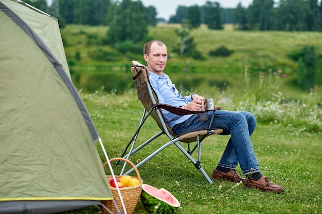 젊은 남자 프리랜서는 숲이나 초원의 캠핑장에서 의자에 앉아 텐트 앞에서 휴식을 취합니다. 여름에 야외 활동입니다. 국립 공원에서 여행하는 모험. 여가, 휴가, 휴식