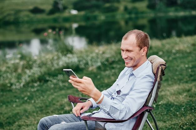 젊은 남자 프리랜서 의자에 앉아 스마트 폰을 사용합니다. 숲이나 초원에서 휴식. 여름에는 원격 작업 및 야외 활동.
