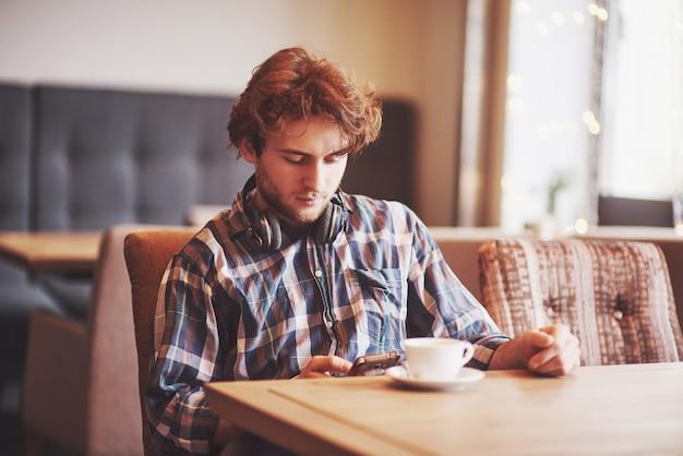 Молодой человек фрилансер с бородой в повседневной одежде сидит в кафе с чашкой кофе