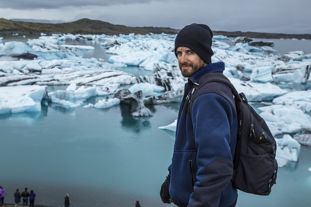 Young man in front of small blue icebergs in jokulsarlon ice lake and very gray sky in iceland