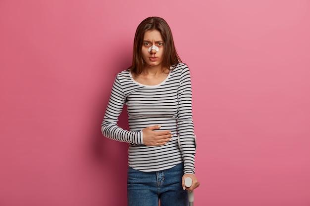 Il giovane aggrotta le sopracciglia per il dolore, sente mal di stomaco, ha un danno fisico al corpo, si sottopone a un programma di recupero riabilitativo, ha sangue dal naso, isolato sul muro rosa. concetto di problemi di salute