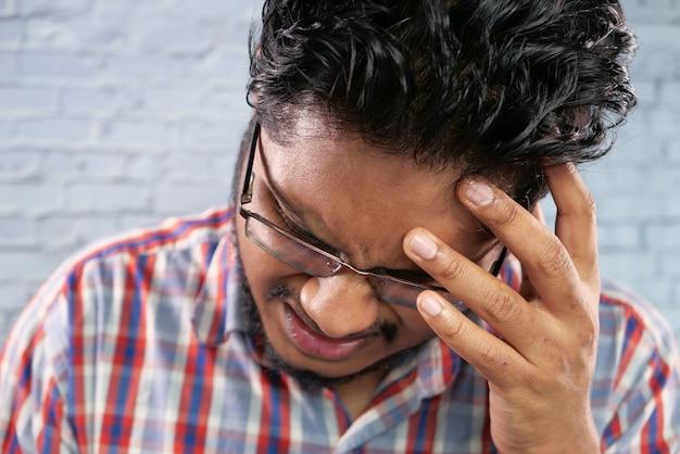 Молодой человек разочарован и страдает головной болью, крупным планом