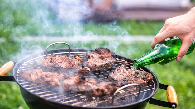 Young man frying meat on the grill and adding beer. greenery around. glamping