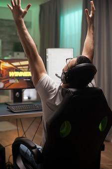 オンラインシューティングゲームで優勝した後、手を挙げて喜びに満ちた青年。