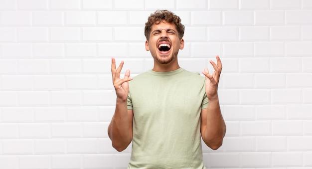 若い男は猛烈に叫び、ストレスを感じ、空中で手を上げてイライラし、なぜ私が