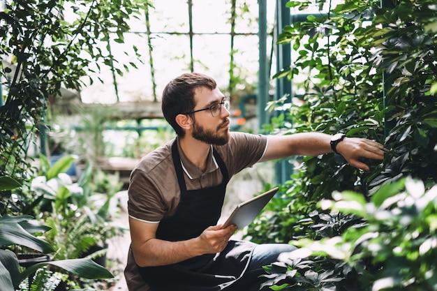 더 나은 품질 관리를 위해 정원 센터에서 일하는 디지털 태블릿으로 안경과 앞치마에 젊은 남자 정원사