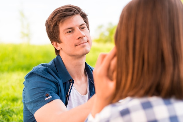 Young man gently stroking woman cheek
