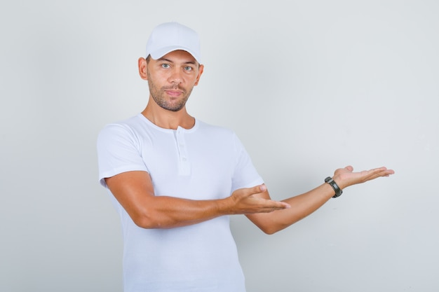 흰색 t- 셔츠, 모자, 전면보기에 환영으로 젊은 남자 몸짓 손.