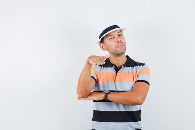 Tシャツと帽子でフラットにするように身振りで示す若い男と注意深く見える