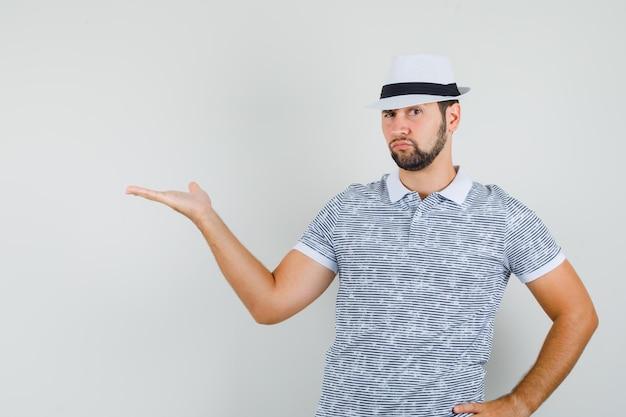 Молодой человек жестикулирует как приветствие или показывает что-то в полосатой футболке, шляпе и смотрит внимательно, вид спереди.