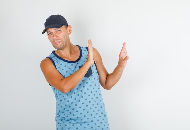 Young man gesturing no sign in blue singlet, cap and looking disgusted