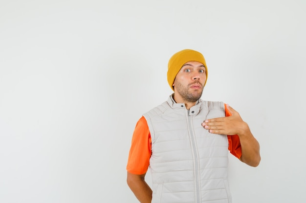 「誰、私?」と尋ねるために身振りで示す若い男。 tシャツ、ジャケット、帽子で困惑しているように見えます。正面図。