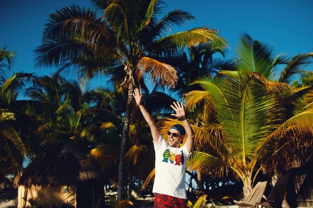 Молодой человек жестикулирует триумф с поднятыми руками на фоне пальм