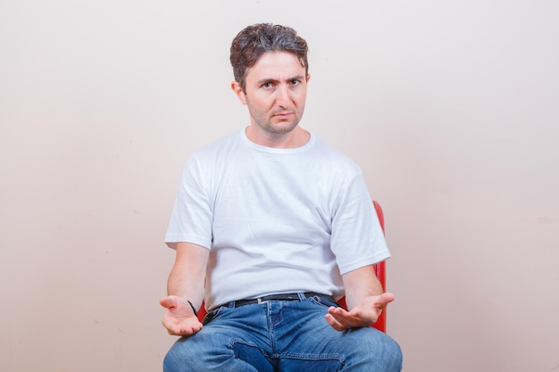 Tシャツ、ジーンズ、混乱して椅子に座って身振りで示す若い男