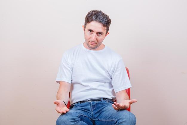 젊은 남자가 티셔츠, 청바지에 의자에 앉아 혼란스러워하는 동안 몸짓