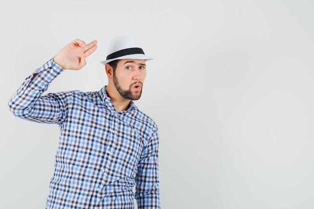 チェックシャツ、帽子、自信を持って、正面図で手と指で身振りで示す若い男。